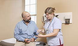 Nurse explaining the use of diabetic equipment to a patient