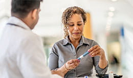 Woman looking at insulin pen while doctor looks at her