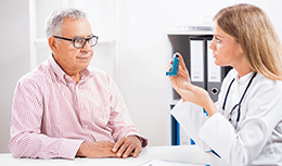 Doctor talking to a patient with an inhaler