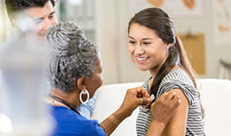 Teenage girl getting a vaccine in an office