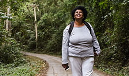 Senior tourist woman walking in nature park