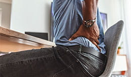 Man holding his back in pain while sitting on work chair