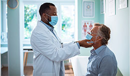 Male physician looking at elderly male patient
