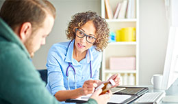 Physician talking with patient, writing down notes