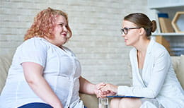 Physician holding hand and discussing with patient with obesity