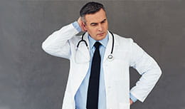 Physician standing by themselves, thinking, holding his head with one hand