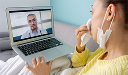 girl, blowing her nose in bed speaking with physician virtually