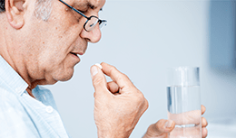 Senior man swallowing pill