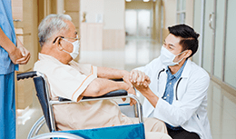 Physician checking on elder patient sitting on wheelchair
