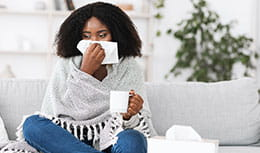 woman blowing her nose with cup of tea