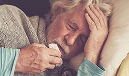 older man in bed with flu