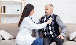 physician checking elder patient's heart with stethoscope