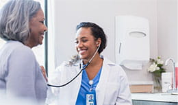 Physician checking elder patient hear with stethoscope