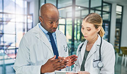 Two physicians looking at a clipboard, while one explains to other physician