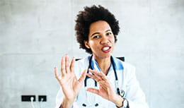 Physician holding both arms up as if she is about to explain a scenario