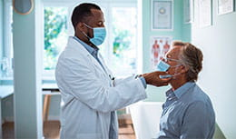 physician performing medical exam to elder patient sitting with mask on