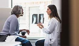 physician describing to elder patient x-ray of foot
