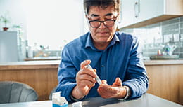 Senior male puncturing finger for test