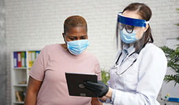 Doctor in protective shield mask talks to obese black woman