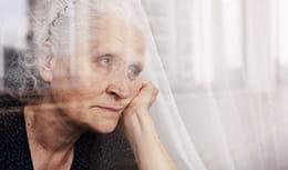 Senior female looking outside a window in deep gaze