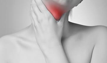 woman holding sore throat