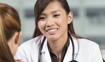 asian doctor in friendly consult with female patient