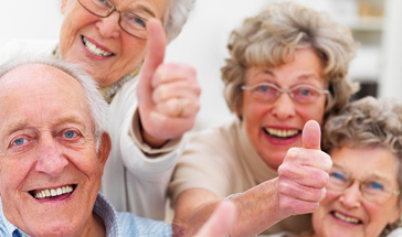 four elderly people looking jovial