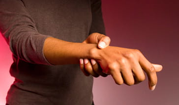 black woman holding right wrist in pain