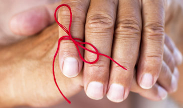 woman with red ribbon tied on pointer finger