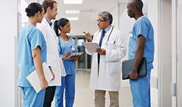 Five doctors discussing patient.